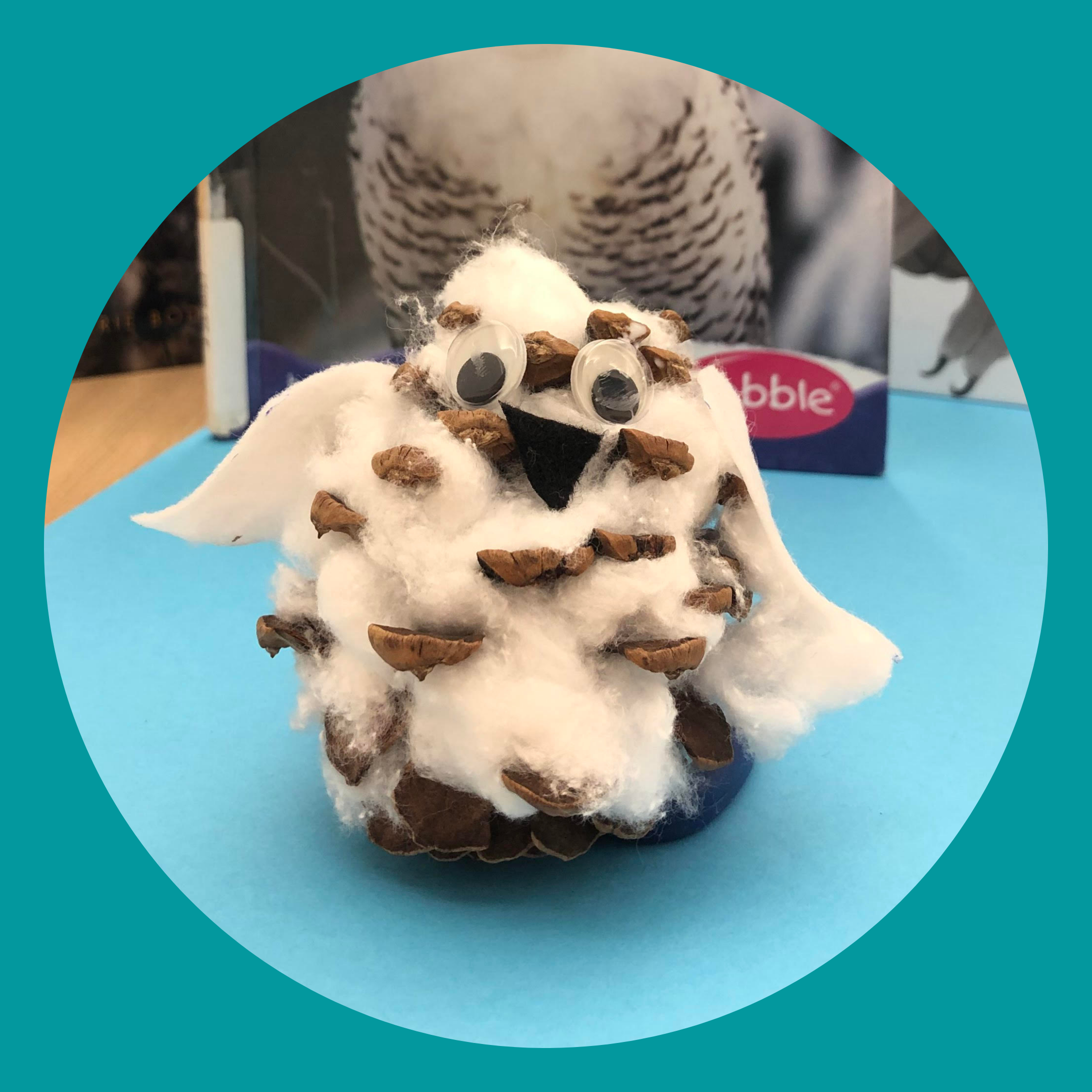 Snowy owl craft made out of a pinecone