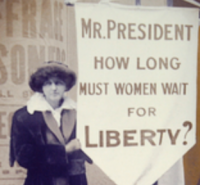 Suffragette with sign Mr. President How long must women wait for liberty?